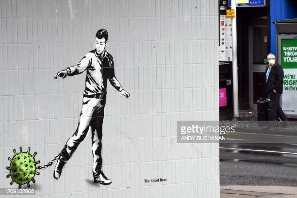 Man wearing a protective face mask walks near a Coronavirus-inspired piece of graffiti in Glasgow on April 4 as life in Britain continues during the...