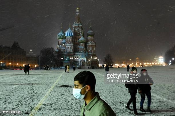 Man wearing a protective face mask walks on a snow-covered Red Square in downtown Moscow on November 26 amid the COVID-19 coronavirus pandemic. -...