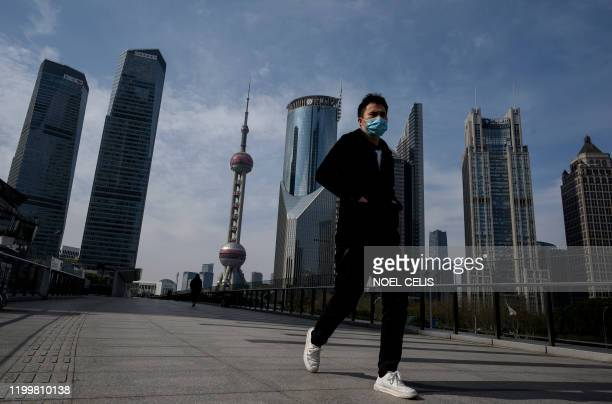 Man wearing a protective face mask walks on an overpass in Lujiazui financial district in Shanghai on February 10, 2020. - The death toll from the...