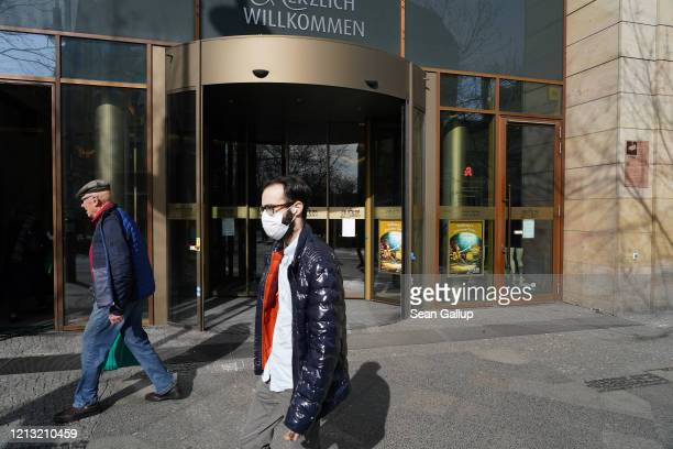 Man wearing a protective face mask walks past a mostly-closed shopping center following a city ordinance temporarily closing all non-essential shops...