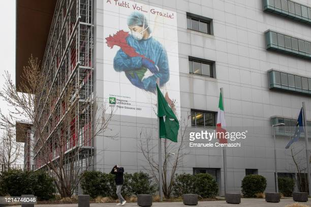 Man, wearing a protective face mask, walks past a mural dedicated to all Italian medical workers depicting a nurse cradling Italy and reading 'To All...