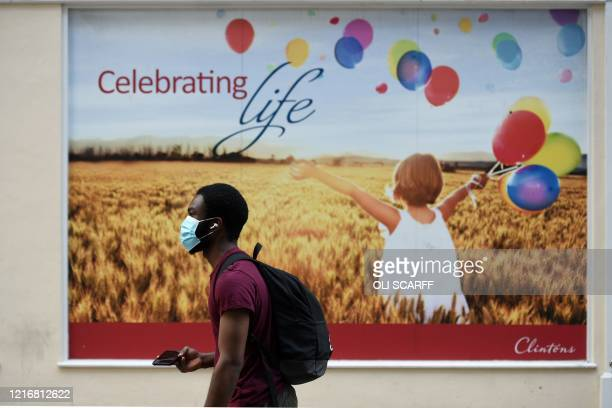 A man wearing a protective face mask walks past a poster in the street in Leeds northern England following the easing of the lockdown restrictions...