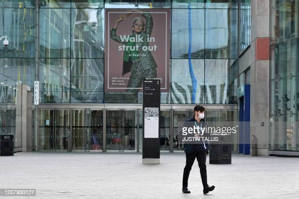 Man wearing a protective face mask walks past a quiet Bullring Shopping Centre in Birmingham in central England on the morning of March 21 a day...