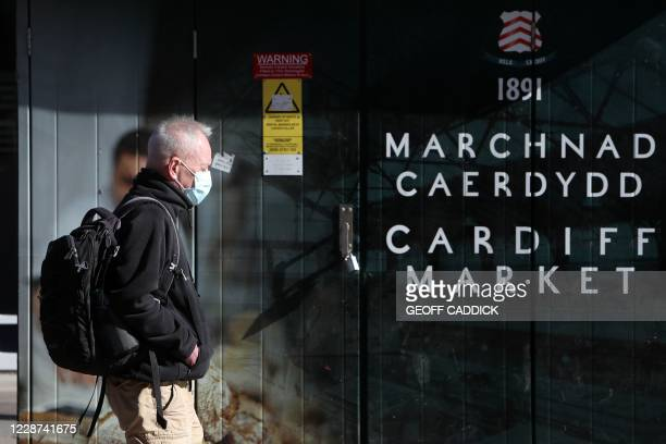 Man wearing a protective face mask walks past a sign for Cardiff Market in Cardiff, south Wales on September 27 during preparations for the...