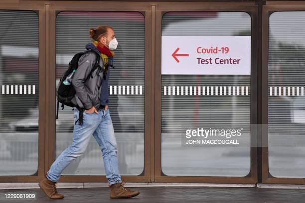 Man wearing a protective face mask walks past a sign indicating a testing centre for the novel coronavirus at Tegel Airport in Berlin on October 14,...