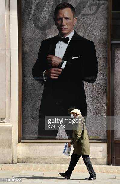 Man wearing a protective face mask walks past an image of James Bond actor Daniel Craig in the window of the Omega Boutique on Regents Street on the...