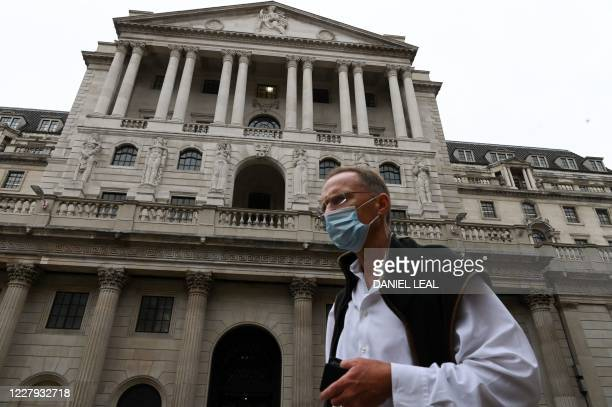 A man wearing a protective face mask walks past the Bank of England in central London on August 6 2020 Britain's economic downturn fuelled by the...