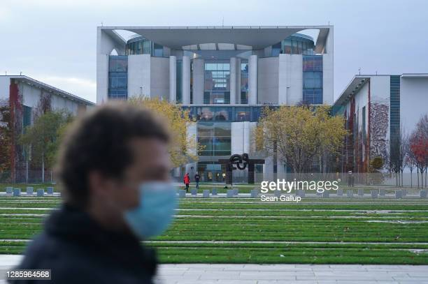 Man wearing a protective face mask walks past the Chancellery, where inside German Chancellor Angela Merkel was holding a virtual meeting with...