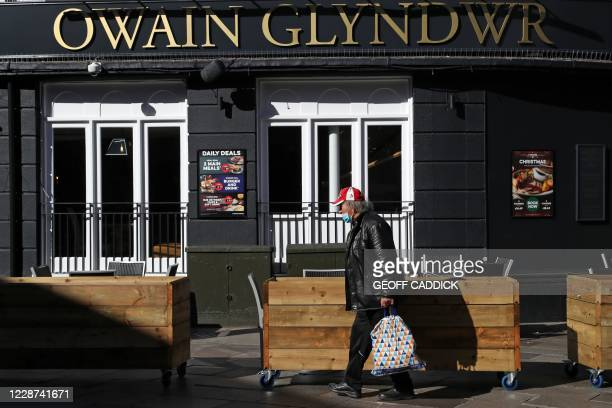 Man wearing a protective face mask walks past the Owain Glyndwr pub in Cardiff, south Wales on September 27 during preparations for the reinstatement...