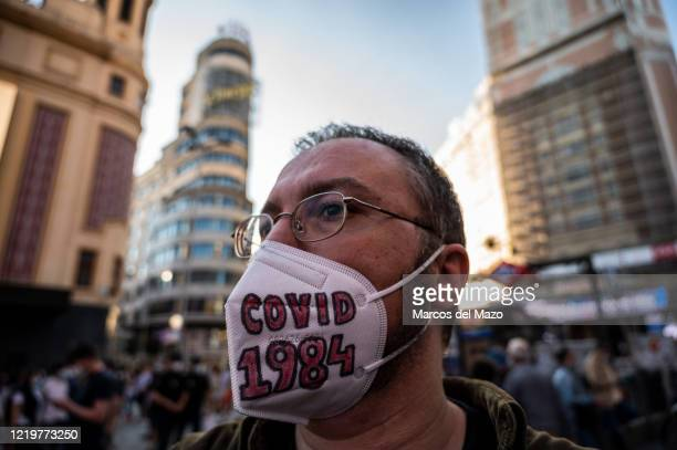 Man wearing a protective face mask with the letters 'covid 1984', alluding to George Orwell's novel, protesting against new normality and New World...
