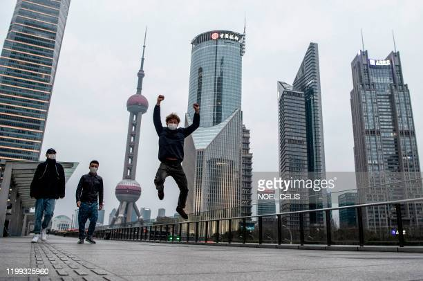 Man wearing a protective facemask jumps as other people walk on an overpass in Lujiazui financial district in Pudong in Shanghai on February 8, 2020....