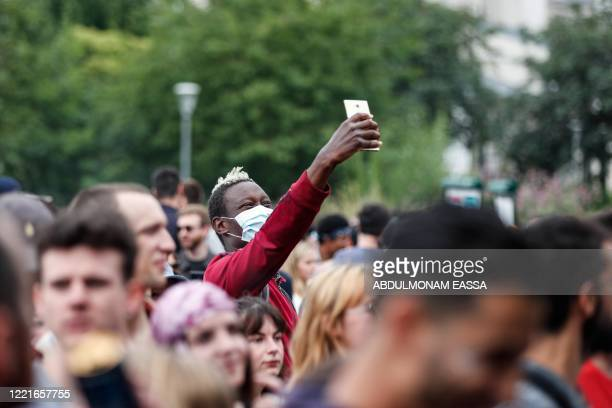Man wearing a protective facemask takes pictures with his mobile phone as he attends, among other people, the French midsummer Festival of Music...