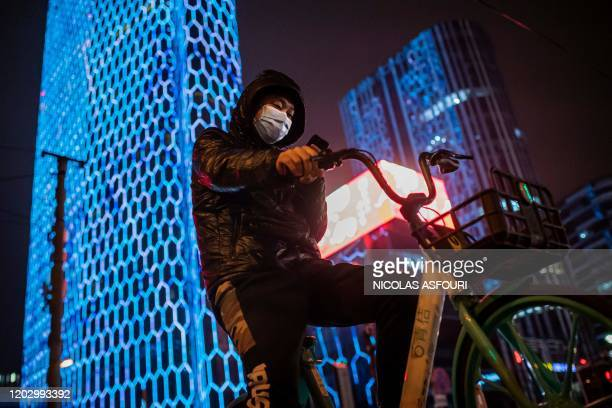 Man wearing a protective facemask to protect against the COVID-19 coronavirus browses his smartphone on a street as he rides a shared bicycle in...