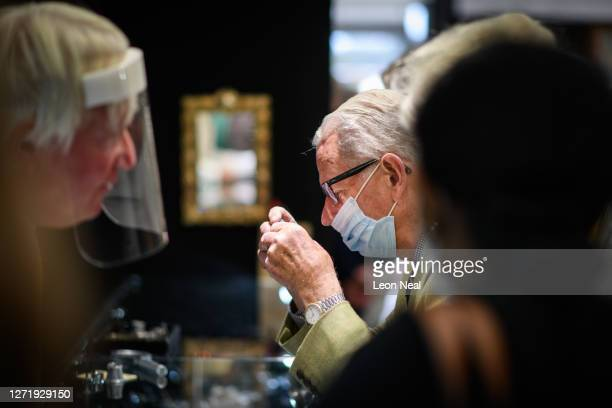 Man wearing a protective facemask uses a jeweller's loupe to examine a small piece of jewellery as he browses the exhibitor's displays at Petworth...
