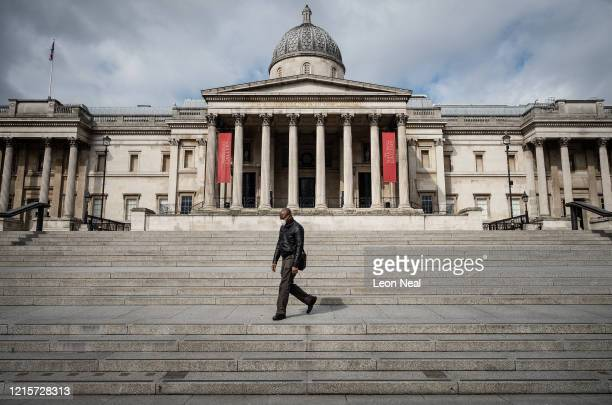 Man wearing a protective face-mask walks through a deserted Trafalgar Square on March 30, 2020 in London, England. The Coronavirus pandemic has...