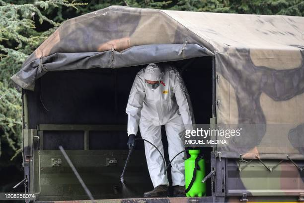 Man wearing a protective gear sprays disinfectant in one of the Italian Army trucks parked on March 26, 2020 at the Monumental Cemetery of Bergamo,...