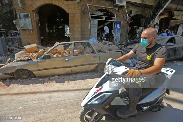 A man wearing a protective mask against the coronavirus rides his motorbike past damaged cars and shops in Beirut's commercial Gemmayzeh district one...