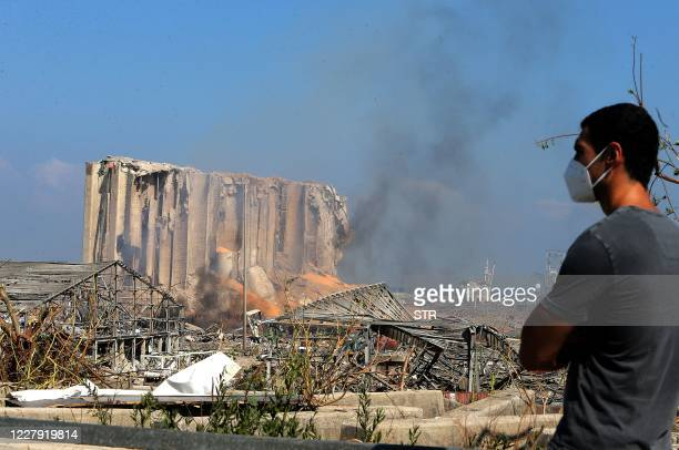 Man wearing a protective mask against the coronavirus stands across the road from the damaged grain silos of Beirut's harbour August 5 one day after...