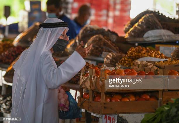 Man wearing a protective mask amid the COVID-19 pandemic, picks tomatoes at a produce market in Dubai in the United Arab Emirates, on September 10,...