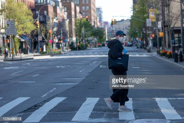 A man wearing a protective mask and gloves walks through an empty street amid the coronavirus pandemic on April 22 2020 in New York City United...