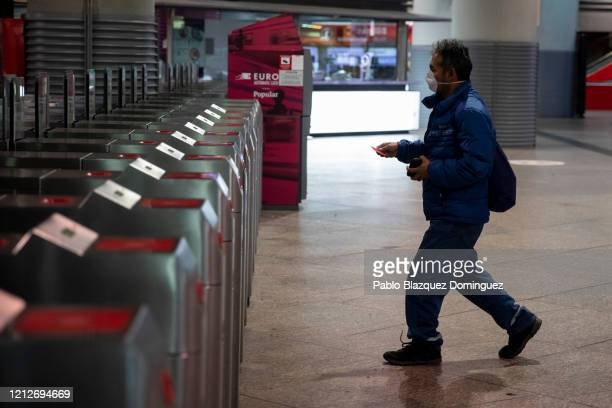 Man wearing a protective mask crosses the doors at Atocha train station as the country works to stop the spread of the coronavirus on March 16, 2020...