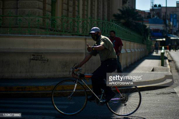 A man wearing a protective mask gestures as he rides his bike through an empty street on March 23 2020 in San Salvador El Salvador Three cases of...
