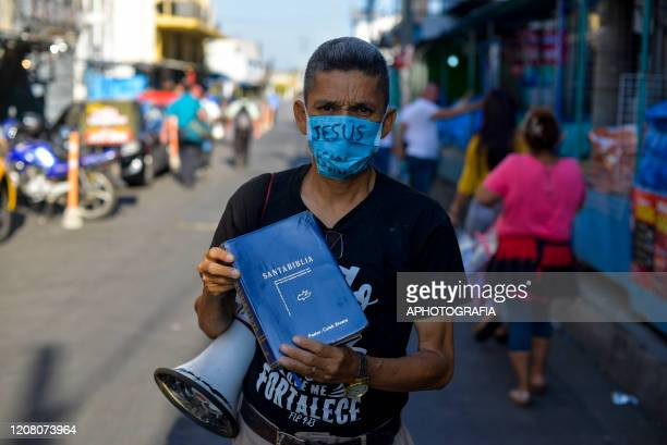 A man wearing a protective mask holds a bible as he preaches in downtown San Salvador on March 23 2020 in San Salvador El Salvador Three cases of...