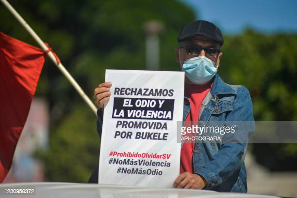 Man wearing a protective mask holds up a sign against hate speech during the funeral of Juan de Dios Tejada member of the FMLN , at La Bermeja...