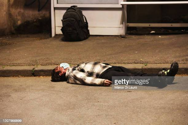 A man wearing a protective mask is on the ground unconscious near a bus stop before being helped by medical personnel as the spread of the...