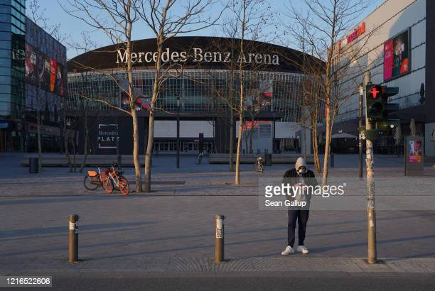Man wearing a protective mask looks at his smartphone while standing in front of the Mercedes-Benz Arena, a spot that under normal circumstances...