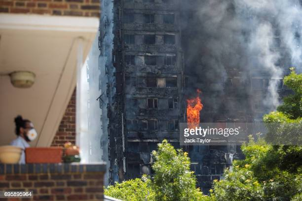 A man wearing a protective mask looks on as smoke rises from the burning building after a huge fire engulfed the 24 storey residential Grenfell Tower...