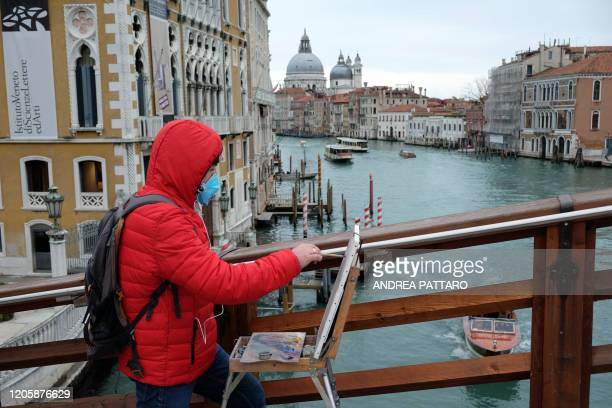 A man wearing a protective mask paint on Accademia bridge in Venice on March 8 2020 on March 8 2020 in Venice shows the Grand Canal empty of boats...