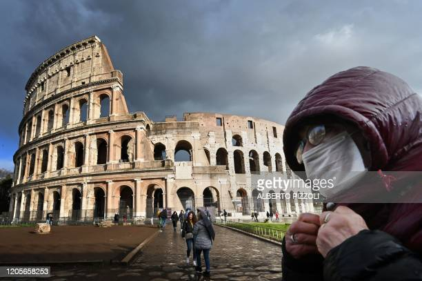 Man wearing a protective mask passes by the Coliseum in Rome on March 7, 2020 amid fear of Covid-19 epidemic. - Italy on March 6, 2020 reported 49...