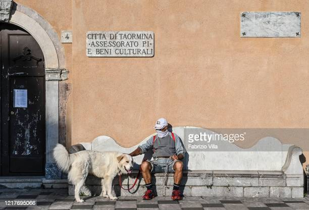 A man wearing a protective mask pats his dog on April 08 2020 in Taormina Italy There have been well over 100000 reported COVID19 cases in Italy and...
