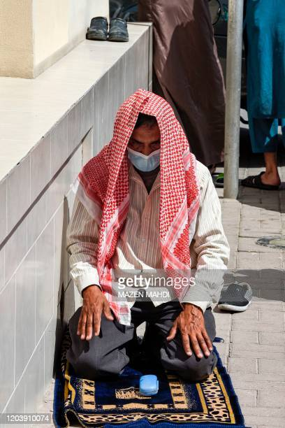 Man wearing a protective mask performs with other men Friday prayers outside a mosque in Bahrain's capital Manama on February 28, 2020. - Bahraini...