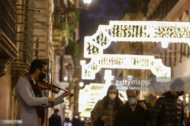 Man wearing a protective mask plays a violin as people crowd Via Condotti, lightened by Christmas lights, in downtown Rome, Italy, on December 19,...