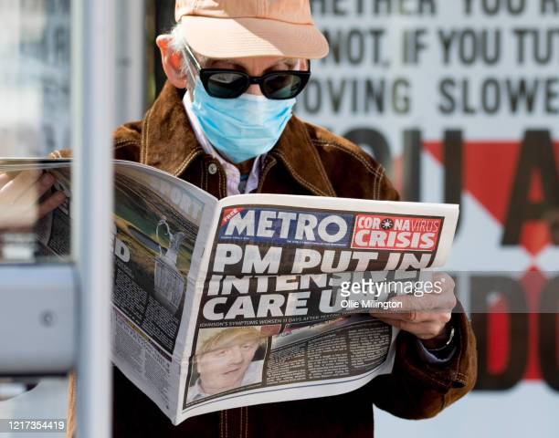 A man wearing a protective mask reads a story in the Metro newspaper about Boris Johnson while standing outside St Thomas' Hospital in Westminster...