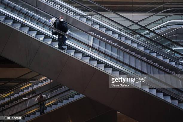 A man wearing a protective mask rides an escalator down to train platforms at nearlydeserted Hauptbahnhof main railway station on March 27 in Berlin...