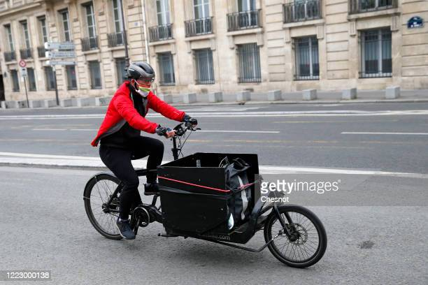A man wearing a protective mask rides his bicycle in the deserted and carfree rue de Rivoli as the lockdown continues due to the epidemic of...