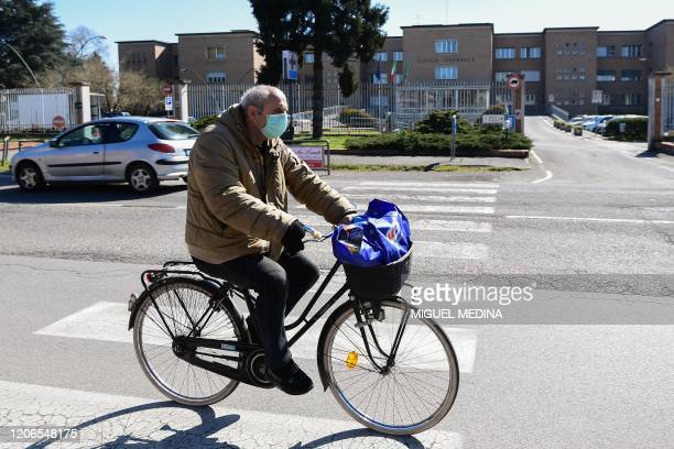 A man wearing a protective mask rides his bicycle past the hospital in Codogno southeast of Milan on March 11 2020 a day after Italy imposed...