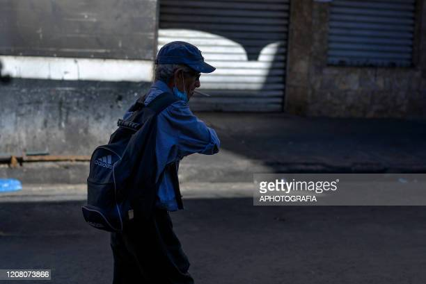 A man wearing a protective mask smokes as he walks through the empty streets of the Historical Center on March 23 2020 in San Salvador El Salvador...