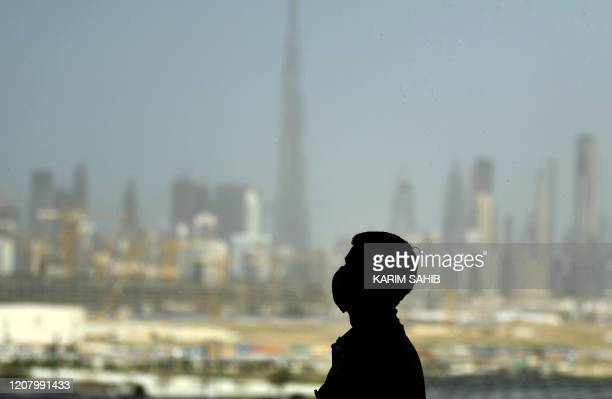 TOPSHOT A man wearing a protective mask stands at a racetrack overlooking Dubai following the UAE's decision to postpone the upcoming Dubai Horse...