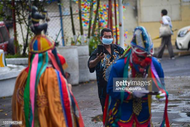 A man wearing a protective mask takes a picture during Historiantes dance as part of international Indigenous day amid Coronavirus pandemic on August...