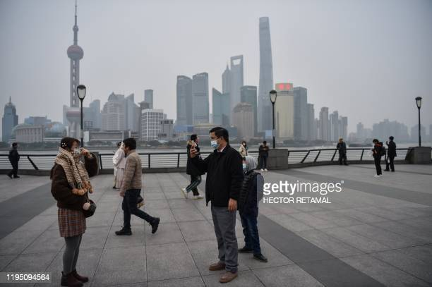 A man wearing a protective mask takes a pictures on the promenade of the Bund along the Huangpu River in Shanghai on January 21 2020 The number of...