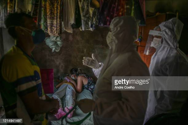 Man wearing a protective mask talks to SOS Funeral team wearing personal protective equipment while a woman cries at the body of his mother, Lucia...