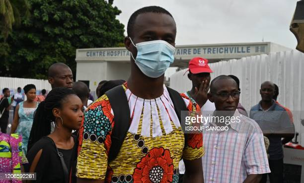 Man wearing a protective mask waits at a bus stop outside Treichville university hospital, on March 11 where the first Ivorian case of new...