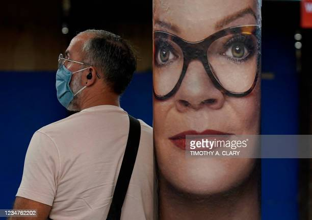 Man wearing a protective mask waits in the subway in New York next to a poster of actress Melissa McCarthy on August 19 to promote the mystery...