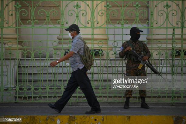 A man wearing a protective mask walks by a soldier on March 23 2020 in San Salvador El Salvador Three cases of COVID19 have been confirmed in El...