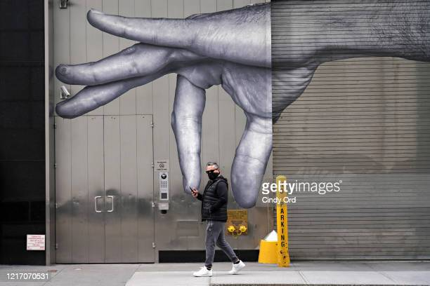 A man wearing a protective mask walks by street art amid the coronavirus pandemic on April 05 2020 in New York City COVID19 has spread to most...
