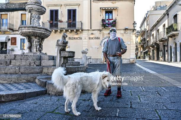 A man wearing a protective mask walks his dog on April 08 2020 in Taormina Italy There have been well over 100000 reported COVID19 cases in Italy and...